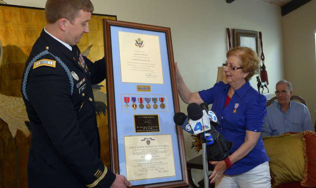 Army Capt. Zachariah L. Fike presents Hyla Merin with a plaque that contains medals, from left, the Bronze Star, the Purple Heart, the Army Good Conduct Medal, American Campaign Medal, European-African-Middle Eastern Campaign Medal and the World War II Victory Medal along with a Silver Star that he pinned to her during a ceremony at her home, Sunday, Feb. 17, 2013, in Thousand Oaks, Calif. The medals were presented posthumously to her father after they were recently discovered in an apartment where Merin's mother and aunts had once lived. (AP Photo/Mark J. Terrill)