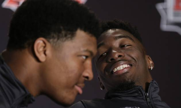 Florida State wide receiver Kenny Shaw, right, looks over at quarterback Jameis Winston during a news conference on Friday, Jan. 3, 2014 in Newport Beach, Calif. Florida State is scheduled to play Auburn on Monday, in the BCS national championship NCAA college football game. (AP Photo/Chris Carlson)