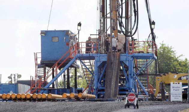 In this photo from June 25, 2012, a crew works on a gas drilling rig at a well site for shale based natural gas in Zelienople, Pa. Some experts say the evidence surrounding questions that gas drilling could be ruining the air and polluting water and making people sick is sketchy and inconclusive, but a lack of serious funding is delaying efforts to resolve those pressing questions and creating a vacuum that could lead to a crush of lawsuits. (AP Photo/Keith Srakocic)