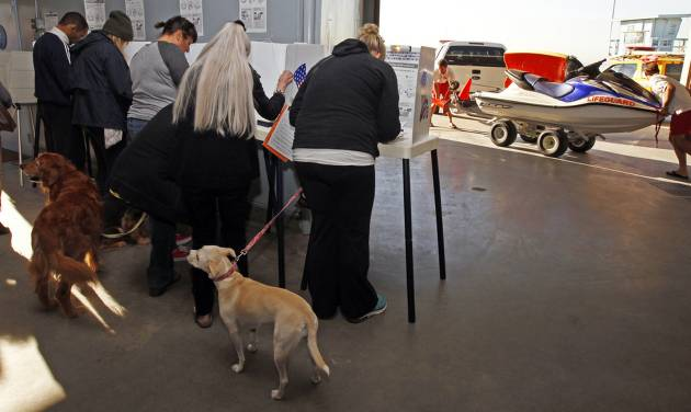 Voters cast ballots as lifeguards maneuver a personal watercraft at the polling place at the Venice Beach lifeguard headquarters in Los Angeles Tuesday, Nov. 6, 2012. After a grinding presidential campaign, Americans are heading into polling places across the country.(AP Photo/Reed Saxon)