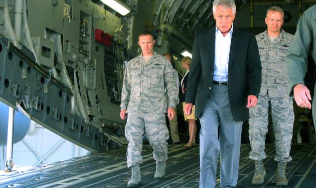 In this photo taken July 17, 2013, Defense Secretary Chuck Hagel, flanked by Air Force personnel, walks down the rear ramp of a C-17 at Joint Base Charleston near Charleston, S.C., on the last day of a three-day trip to visit bases in the Carolinas and Florida. When Hagel told civilian Department of Defense workers on the base that job furloughs, that have forced a 20% pay cut on most of the military's civilian workforce, will likely continue next year, and may get even worse, the audience softly gasped in surprise and gave a few depressed low whistles. He said that if the department has to absorb another $52 billion in cuts next year because of the federal sequester, there will likely be layoffs instead of furloughs. (AP Photo/Bruce Smith)