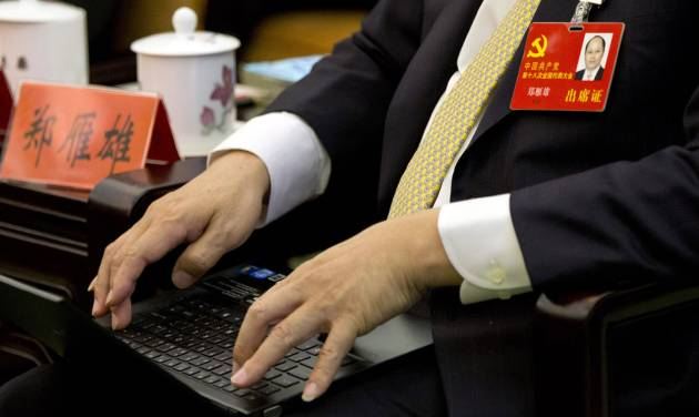 In this Nov. 9, 2012 photo, Communist Party delegate Zheng Yanxiong uses his laptop during a group discussion meeting as part of the 18th Communist Party Congress at the Great Hall of the People in Beijing, China. During China's last party congress, the cadres in charge of the world's most populous nation didn't know a hashtag from a hyperlink. But five years on, there's a new message from Beijing: The political transition will be microblogged. (AP Photo/Alexander F. Yuan)