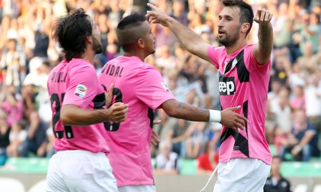 Juventus Mirko Vucinic, of Montenegro, right, celebrates with teammates Arturo Vidal, center, and Andrea Pirlo after scoring during a Serie A soccer match between Udinese and Juventus at the Friuli Stadium in Udine, Italy, Sunday, Sept. 2, 2012. (AP Photo/Paolo Giovannini)