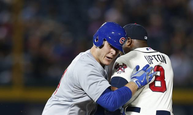 Chicago Cubs' Anthony Rizzo, left, is tagged out by Atlanta Braves left fielder Justin Upton (8) after being caught in a rundown between first and second base in the fourth inning of a baseball game on Saturday, May 10, 2014, in Atlanta. (AP Photo/John Bazemore)