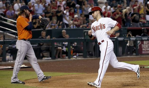 Arizona Diamondbacks' Ender Inciarte, right, scores a run as Houston Astros pitcher Josh Fields back up home plate during the seventh inning of a baseball game on Tuesday, June 10, 2014, in Phoenix. (AP Photo/Ross D. Franklin)