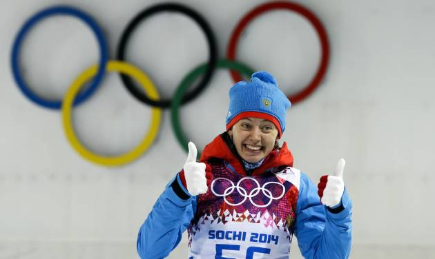 Second placed Russia's Olga Vilukhina gives a thumbs up during the flower ceremony after the women's biathlon 7.5k sprint, at the 2014 Winter Olympics, Sunday, Feb. 9, 2014, in Krasnaya Polyana, Russia. (AP Photo/Lee Jin-man)