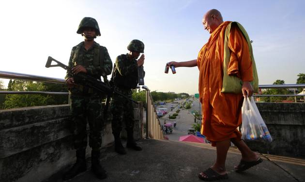 A Buddhist monk offers energy drink to Thai soldiers guarding a pedestrian overfly near the site where pro-government demonstrators stage a rally on the outskirts of Bangkok, Thailand Tuesday, May 20, 2014. As Thailand finishes its first day under martial law, there are some questions that the military action raises. Many wonder if the arrival of soldiers in the streets of Bangkok constitutes a military coup, and how it affects people living in the Thai capital or visiting.  (AP Photo/Wason Wanichakorn)