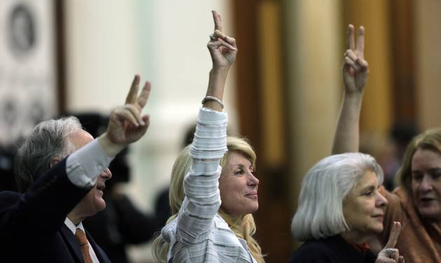 "FILE -  In this Tuesday, June 25, 2013, file photo, Sen. Wendy Davis, D-Fort Worth, center, holds up two fingers to signal a ""No"" vote as the session where tshe tried to filibuster an abortion bill draws to a close, in Austin, Texas. Hundreds of abortion rights activists ensured that the first special legislative session descended into chaos. Now, Texas Gov. Rick Perry has convened a second one and urged abortion opponents to respond with mobilizations of their own. (AP Photo/Eric Gay, File)"
