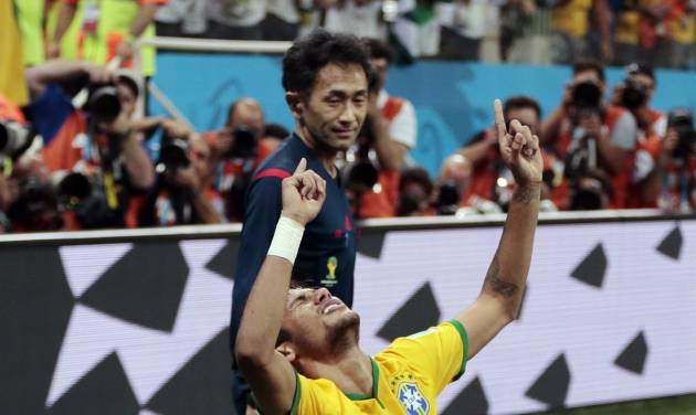 In this Thursday, June 12, 2014 photo, referee Yuichi Nishimura from Japan watches as Brazil's Neymar celebrates his second goal on a penalty kick during the group A World Cup soccer match between Brazil and Croatia, the opening game of the tournament, in the Itaquerao Stadium in Sao Paulo, Brazil.  (AP Photo/Ivan Sekretarev)