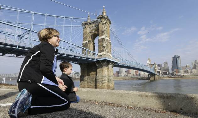 This April 9, 2013 photo shows Yvonne Parmley kneeling with her grandson, Finley MacKay, as they look towards downtown Cincinnati next to the Roebling Suspension Bridge over the Ohio River in Covington, Ky. The bridge was the model for New York City's Brooklyn Bridge. (AP Photo/Al Behrman)