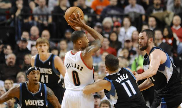Minnesota Timberwolves' Jose Barea (11) and Kevin Love, right, defend a drive by Portland Trail Blazers' Damian Lillard (0) during the first half of an NBA basketball game in Portland, Ore., Friday, Nov. 23, 2012. At left is Timberwolves' Dante Cunningham. (AP Photo/Greg Wahl-Stephens)