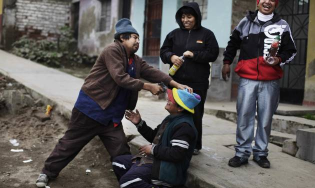 In this Aug. 8, 2013 photo, a man playfully points a toy gun at his friend's forehead, as the four unemployed and homeless Peruvians drink alcohol while passing the time in the Villa Maria del Triunfo , Lima, Peru. Peru's capital is a city of contrasts. It can be hospitable, orderly and picturesque when seen through the eyes of a foreign tourist. But also squalid and chaotic in the crowded impoverished peripheries of this capital of 9 million, many of them transplants from the Andean highlands who pour in every day, unprepared for  life in the big city. (AP Photo/Rodrigo Abd)