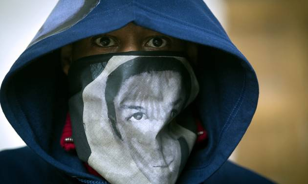 """A man wears a hoodie and a scarf with the likeness of Trayvon Martin during a """"One Thousand Hoodies March for Trayvon Martin"""" event Thursday, March 29, 2012 at the University of Minnesota campus in Minneapolis. Martin, a Florida teenager, was wearing a hoodie when he was shot and killed by a neighborhood watch volunteer. (AP Photo/The Star Tribune, Renee Jones Schneider) MANDATORY CREDIT; ST. PAUL PIONEER PRESS OUT; MAGS OUT; TWIN CITIES TV OUT"""