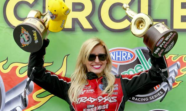 Funny Car driver Courtney Force hoists up her trophies for winning the NHRA Kansas Nationals auto race and being the 100th professional win for women drivers in the NHRA after defeating Cruz Pedregon in the finals at Heartland Park in Topeka, Kan., on Sunday, May 25, 2014. (AP Photo/The Topeka Capital Journal, Chris Neal)