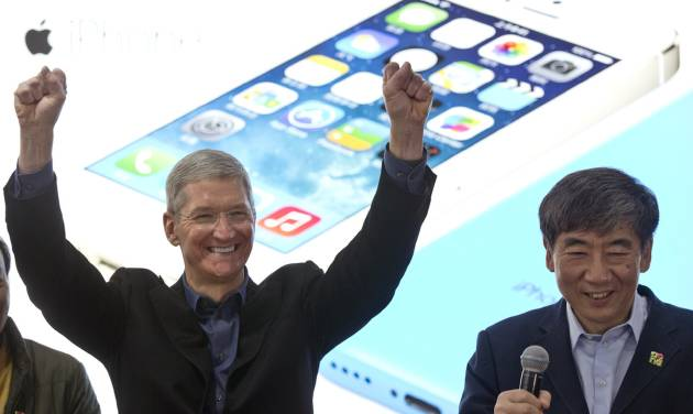 FILE - In this Jan. 17, 2014 file photo, Apple's CEO Tim Cook, left, gestures as China Mobile Chairman Xi Guohua smiles during a promotional event that marks the opening day of sales of China Mobile's 4G iPhone 5s and iPhone 5c in Beijing, China. Soaring sales of iPhones in China, Russia, India and Brazil during the April-June 2014 period helped Apple overcome softening demand for the device in the U.S. and Europe, where consumers seem to be more interested in waiting for the autumn release of a new iPhone that's expected to feature a larger screen. (AP Photo/Alexander F. Yuan, File)