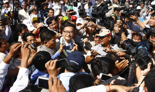 Opposition Cambodia National Rescue Party leader Sam Rainsy, center, is surrounded by members of press upon arrival at Phnom Penh International Airport, in Phnom Penh, Cambodia, Friday, Aug. 16, 2013. Cambodia's main opposition party filed formal complaints Wednesday over the results of last month's general election, challenging the victory of the ruling Cambodian People's Party and alleging widespread irregularities. The complaints should delay ratification of the results by the National Election Committee until sometime before Sept. 8. (AP Photo/Heng Sinith)