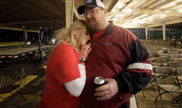 Brad Pustejovsky is hugged by his wife Dolores as he answers a reporters question about his brother Joey Pustejovsky, Thursday, April 17, 2014, in West, Texas. Joey was a volunteer firefighter in West, who was killed one year ago fighting a fire at a fertilizer plant that would later explode. AP Photo/Tony Gutierrez)
