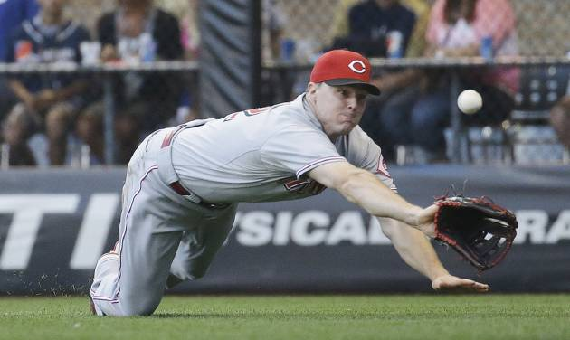 Cincinnati Reds' Jay Bruce dives but can't catch a ball hit by Milwaukee Brewers' Carlos Gomez during the fifth inning of a baseball game Wednesday, July 23, 2014, in Milwaukee. (AP Photo/Morry Gash)