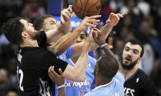 Minnesota Timberwolves forward Kevin Love, left, battles Los Angeles Clippers forward Blake Griffin, second from left, center Ryan Hollins, center, and guard Chris Paul, second from right as Timberwolves center Nikola Pekovic, right, of Montenegro, stands near in the first half of an NBA basketball game in Los Angeles on Sunday, Dec. 22, 2013. (AP Photo/Alex Gallardo)