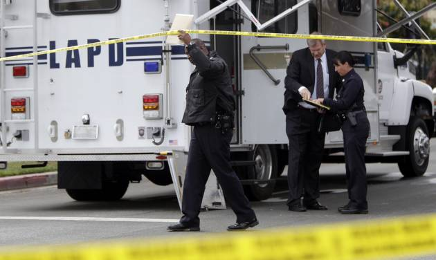 Los Angeles Police Department investigators work at the scene of a shooting of two USC students in Los Angeles on Wednesday, April 11, 2012. Police said a gunman opened fire on a BMW near the University of Southern California campus on Wednesday, killing two international students from China in what may have been a bungled carjacking attempt. (AP Photo Damian Dovarganes)