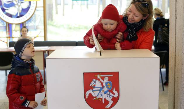 A woman with a child casts her ballot at a polling station during the first round of voting in presidential elections in Vilnius, Lithuania, Sunday May 11, 2014. (AP Photo/Mindaugas Kulbis)