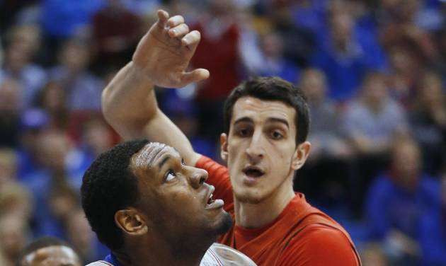 Kansas forward Tarik Black (25) is fouled while covered by Texas Tech forward Dejan Kravic, back, during the first half of an NCAA college basketball game in Lawrence, Kan., Wednesday, March 5, 2014. (AP Photo/Orlin Wagner)