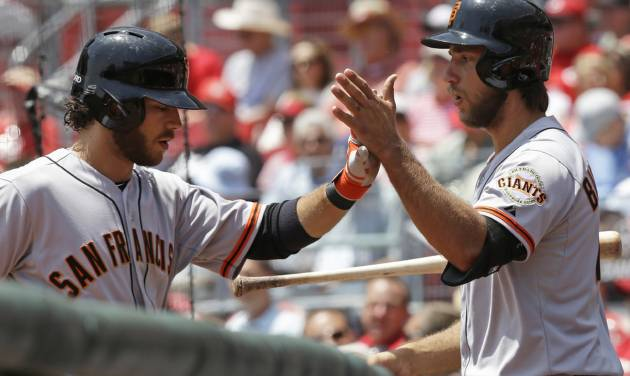 San Francisco Giants starting pitcher Madison Bumgarner, right, congratulates Brandon Crawford after Crawford hit a three-run home run off Cincinnati Reds starting pitcher Mike Leake in the fourth inning of a baseball game, Thursday, June 5, 2014, in Cincinnati. (AP Photo/Al Behrman)