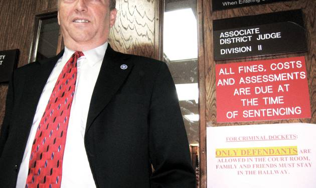 David Starkey stands next to a sign on the door to District Judge Dwayne Steidley's courtroom in Rogers County that tells people the public isn't welcome. By Tony Thornton