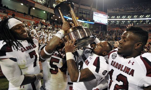 South Carolina players Jadeveon Clowney (7), Shaq Wilson (54), Akeem Auguste (3) and Brison Williams (12) carry the Palmetto Bowl Trophy after an NCAA college football game against Clemson, Saturday, Nov. 24, 2012, in Clemson, S.C. South Carolina won 27-17. (AP Photo/Rainier Ehrhardt)