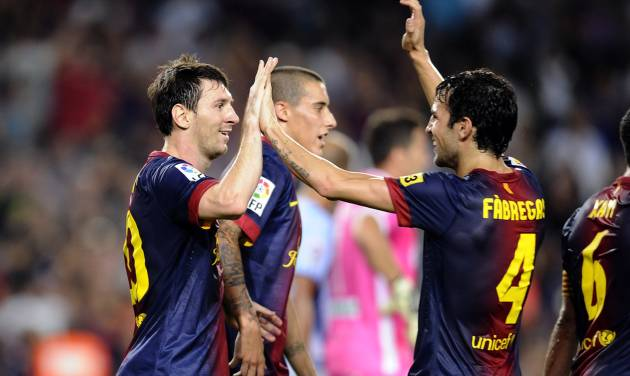 FC Barcelona's Lionel Messi from Argentina, left, reacts after scoring with his teammate Cesc Fabregas, right, against Granada during a Spanish La Liga soccer match at the Camp Nou stadium in Barcelona, Spain, Saturday, Sept. 22, 2012. (AP Photo/Manu Fernandez)