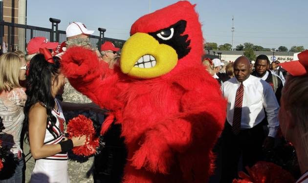 File-This Oct. 10, 2013, file photo shows the Cardinal Bird mascot leading then football coach Charlie Strong, right, and the team into the stadium before Louisville's NCAA college football game against Rutgers in Louisville, Ky.  The musical chairs of conference realignment returns this this week, with more major colleges taking new seats. On Tuesday, July 1, 2014, 12 FBS teams officially switch places, including Louisville in the Atlantic Coast Conference and Maryland and Rutgers in the Big Ten. (AP Photo/Garry Jones, File)