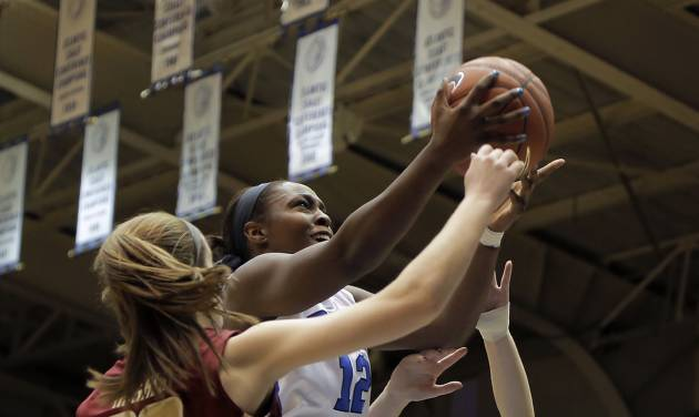 Duke's Chelsea Gray (12) drives to the basket between Boston College's Kelly Hughes (23) and Victoria Lesko, right, during the first half of an NCAA college basketball game in Durham, N.C., Sunday, Jan. 12, 2014. (AP Photo/Ted Richardson)