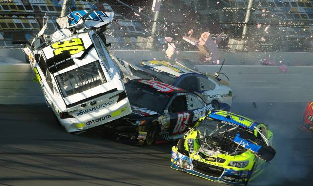 Parker Kligerman (30) gets airborne as he is involved in a crash with Ryan Truex (83), Paul Menard (27), and Dave Blaney (77) during practice for Sunday's NASCAR Daytona 500 Sprint Cup Series auto race at Daytona International Speedway, Wednesday, Feb. 19, 2014. (AP Photo/News-Journal, Nigel Cook)