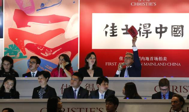 A Christie's employee raises a card to bid on behalf of a client on the phone during an auction in Shanghai, China Thursday, Sept. 26, 2013. Christie's drew the elite of China closer into its orbit with an auction Thursday of works by Pablo Picasso, Andy Warhol and others in Shanghai, the first time any foreign auction house has held such a sale on the mainland without having to go through intermediaries. (AP Photo)