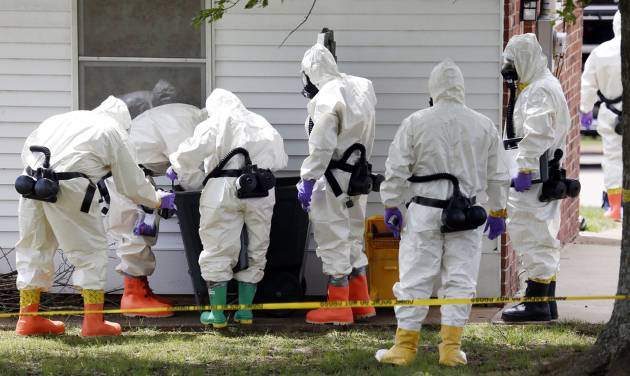 Federal agents wearing hazardous material suits and breathing apparatus inspect the trash can outside the West Hills Subdivision house of Paul Kevin Curtis in Corinth, Miss., Friday, April 19, 2013. Curtis is in custody under the suspicion of sending letters covered in ricin to the U.S. President Barack Obama and U.S. Sen. Roger Wicker, R-Miss. (AP Photo/Rogelio V. Solis)