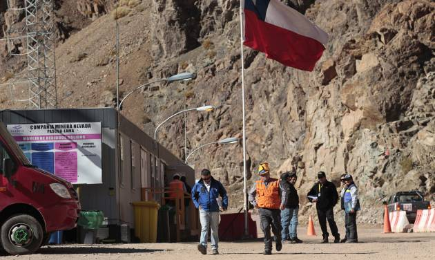 """In this May 23, 2013 photo, security officers walk away from the entrance of the Barrick Gold Corp's Pascua-Lama facilities, in northern Chile. Chile's environmental regulator blocked Barrick Gold Corp.'s $8.5 billion Pascua-Lama project on Friday, May 24, 2013, and imposed its maximum fine on the world's largest gold miner, citing """"very serious"""" violations of its environmental permit as well as a failure by the company to accurately describe what it had done wrong. (AP Photo/Jorge Saenz)"""