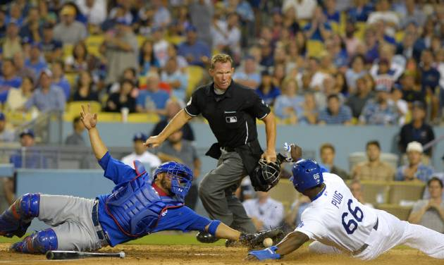 Los Angeles Dodgers' Yasiel Puig, right, scores on a fielders' choice by Hanley Ramirez as Chicago Cubs catcher Welington Castillo, left, reaches to tag him as home plate umpire Jim Wolf looks on during the sixth inning of a baseball game, Friday, Aug. 1, 2014, in Los Angeles. (AP Photo/Mark J. Terrill)