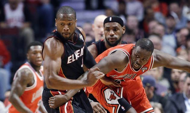 Miami Heat guard Dwyane Wade, left, forward LeBron James, center, and Chicago Bulls forward Luol Deng watch a loose ball during the first half of an NBA basketball game in Chicago on Wednesday, March 27, 2013. (AP Photo/Nam Y. Huh)