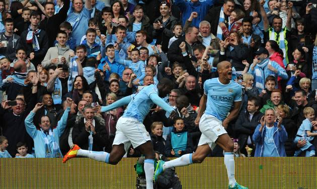 Manchester City's Vincent Kompany, right, celebrates after scoring against West Ham during the English Premier League soccer match between Manchester City and West Ham United at the Etihad Stadium, Manchester, England, Sunday, May 11, 2014. (AP Photo/Rui Vieira)