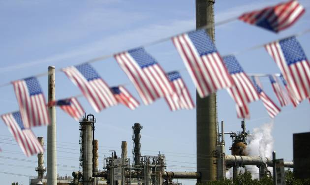 "FILE - In this April 30, 2008 file photo, American flags are seen near the Shell refinery, in Martinez, Calif. On Weds., Nov. 14, 2012, California's largest greenhouse gas emitters will for the first time begin buying permits in a landmark ""cap-and-trade"" system meant to control emissions of heat-trapping gases and spur investment in clean technologies. The program is a key part of California's 2006 climate-change law, AB32, a suite of regulations that dictate standards for cleaner-burning fuels, more efficient automobiles and increased use of renewable energy. (AP Photo/Ben Margot, File)"
