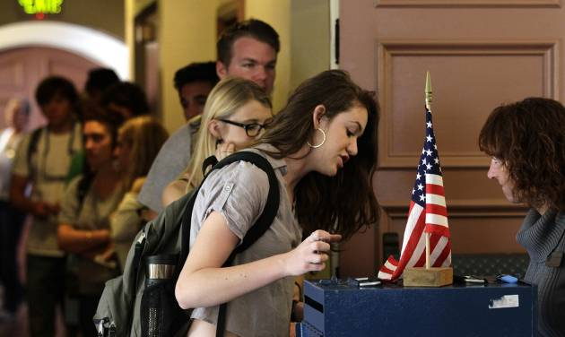 College student Cortney Ratashak, 18, of Littleton, Colo., talks over paperwork with an electoral official before voting in the general election, at a polling station serving the local student population on the campus of the University of Colorado, in Boulder, Colo., Tuesday, Nov. 6, 2012. After a grinding presidential campaign, Americans are heading into polling places across the country.(AP Photo/Brennan Linsley)