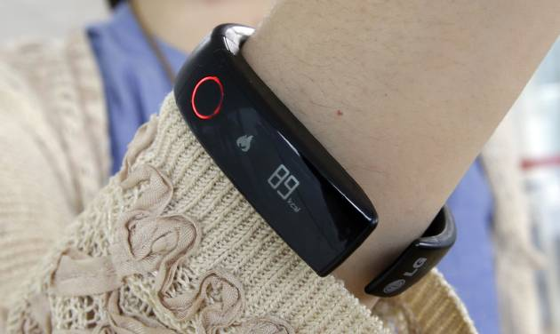 In this June 5, 2014 photo, a reporter shows LG's Lifeband Touch for photographs in Seoul, South Korea. LG Electronics Inc. has entered the fledging market for wearable gadgets with a wristband that tracks workouts and calories burned. (AP Photo/Lee Jin-man)