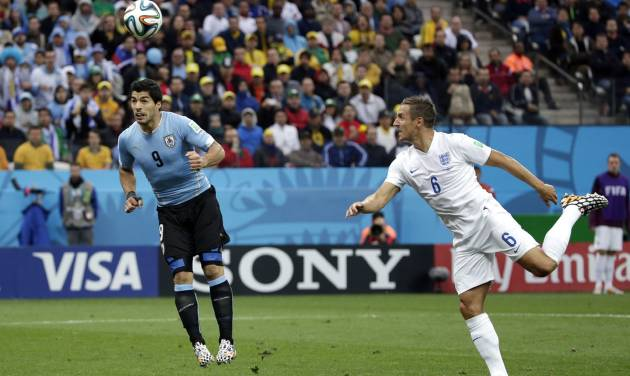 England's Phil Jagielka watches as Uruguay's Luis Suarez heads the ball to score his side's first goal during the group D World Cup soccer match between Uruguay and England at the Itaquerao Stadium in Sao Paulo, Brazil, Thursday, June 19, 2014.  (AP Photo/Felipe Dana)
