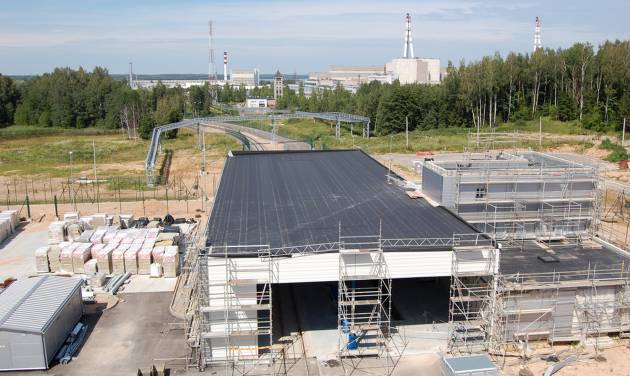 This July 2012 photo shows the gatehouse of the partially-completed nuclear storage facility in Ignalina, Lithuania. Three years after the nuclear plant was shut down due to safety concerns, there is still nuclear fuel inside one of the two reactors. The temporary storage facilities for spent fuel and radioactive waste are four years behind schedule. The problems have prompted threats from the European Union to sever funding and raising concerns that the facility will be around for years, possibly decades, longer than planned. The giant ventilation stacks in the background are part of the nuclear power plant. (AP Photo/Gary Peach)