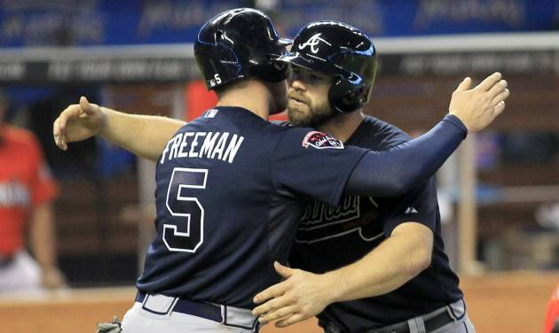 Atlanta Braves catcher Evan Gattis, right, celebrates with teammate Freddie Freeman after they scored on Gattis' game-winning two-run home run in the ninth inning of a baseball game against the Miami Marlins in Miami, Sunday, June 1, 2014. The Braves completed a three-game sweep of the Marlins with a 4-2 win. (AP Photo/Joe Skipper)