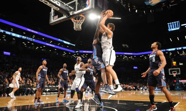 Brooklyn Nets' Brook Lopez (11) shoots over Charlotte Bobcats' DeSagana Diop (2) in the first half of an NBA basketball game on Friday, Dec., 28, 2012 at Barclays Center in New York. (AP Photo/Kathy Kmonicek)