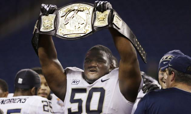 Pittsburgh defensive lineman Tyrone Ezell holds up a wrestling championship belt after the Panthers defeated Bowling Green 30-27 in the Little Caesars Pizza Bowl NCAA college football game, Thursday, Dec. 26, 2013, in Detroit. (AP Photo/Carlos Osorio)