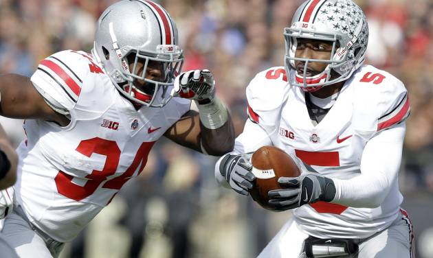 Ohio State quarterback Braxton Miller, right, fakes a hand off to running back Carlos Hyde during the first half of an NCAA college football game in West Lafayette, Ind., Saturday, Nov. 2, 2013. (AP Photo/Michael Conroy)