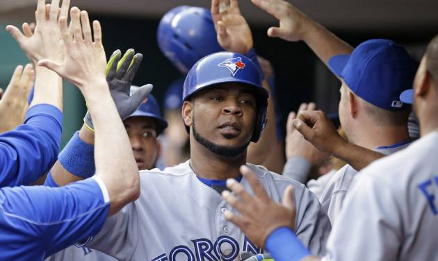 Toronto Blue Jays' Edwin Encarnacion is congratulated in the dugout after hitting a three-run home run off Cincinnati Reds starting pitcher Mat Latos in the third inning of a baseball game, Friday, June 20, 2014, in Cincinnati. (AP Photo/Al Behrman)