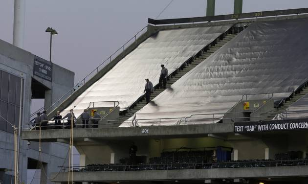 Law enforcement officials walk in the upper deck of O.co Coliseum after an NFL football game between the Oakland Raiders and the Tennessee Titans in Oakland, Calif., Sunday, Nov. 24, 2013. Authorities say a football fan jumped after the game from the third deck of the Oakland Coliseum, injuring herself and a man one level below who tried to catch her. She and the man who tried to catch her were rushed to the hospital for treatment. (AP Photo/Jeff Chiu)